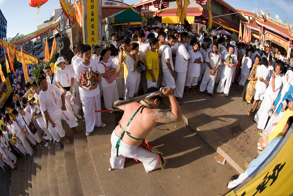 A medium hacks himself in the back with a sword at the entrance to Jui Tui Shrine at the Phuket Vegetarian Festival Street Procession, Phuket Town, Thailand.....** The Phuket Vegetarian Festival celebrates the beginning of Taoist Lent, when devout Chinese abstain from eating all meat and other vices.  The festival takes place on the first 9 days of the 9th lunar month of the Chinese calendar.  Everyone dresses in white and shopkeepers set up small alters with offerings of incense, flowers, candles, fruit, and 9 cups of tea to the 9 emperor deities honored by the festival. ....Mediums bring the 9 gods to earth entering a trance state and piercing themselves with all kinds of objects, climbing knife ladders, and walking on hot coals.  The mediums participate in daily processions through town where they stop at the store front alters, drink one of the 9 cups of tea, and offer blessings to the merchants.  The shopkeepers stand in prayer like fashion respecting the mediums that are temporarily possessed by the deity.  The self torture is done to shift evil from individuals to the mediums and bring the community good luck.....Young men carry alters of the deity images though town which culminates at central locations where merchants cover them with huge strands of firecrackers and larger explosives.  The louder and longer blasts are best to drive away evil spirits.  The experience is deafening and engulfs the men and alters in a painful barrage of fire and smoke.  ....Chinese tour groups come to witness since there is no record of this type celebration of Taoist Lent in China.  The festival is believed to have started when a Chinese theatre troupe fell ill for failing to honor the 9 emperor gods of Taoism.  They were quickly cured when they adhered to the 9 day ritual now held each year promoting inner peace, brightness, and proper hygiene.  ..