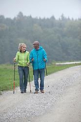 Senior couple hiking with hiking poles, Bavaria, Germany