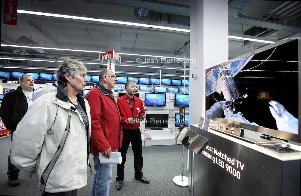 Nederland, Amsterdam , 25 februari 2011..Bezoekers van de Mediamarkt in Amsterdam Noord krijgen van Mediamarkt personeel uitleg omtrent de nieuwste geavanceerde LED televisies. Clients want to know all about the 3D TV. The salesman of Mediamarkt explains.