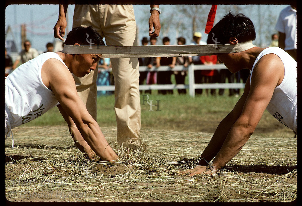 Two men use their heads in Sakha-style tug-of-war match at the midsummer Ysyakh fest; Yakutsk. Russia