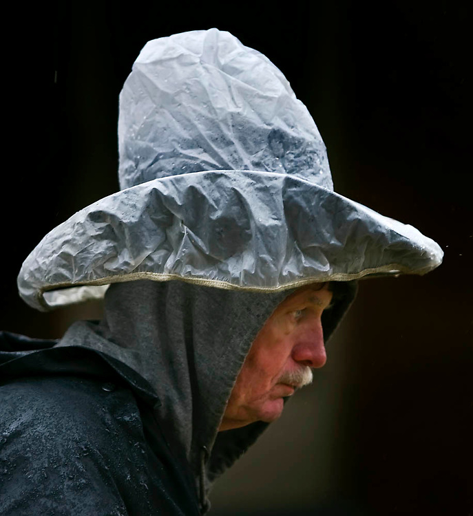 """Mike Prince of Kansas City knew his priorities on a soggy Sunday afternoon on a walk at 38th and Bell...to keep his cowboy hat dry. """"If you spend $100 to $200 (on a hat)....you don't want to screw that up,"""" Prince said about his plastic covering."""
