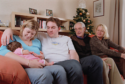 Family group with three generations sitting together in living room,
