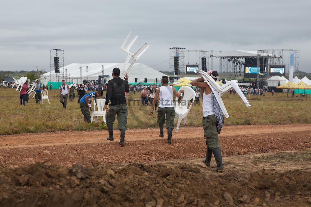 El Diamante, Meta, Colombia - 17.09.2016        <br /> <br /> FARC fighter carring chairs to the opening ceremony of the 10th conference of the marxist FARC-EP in El Diamante, a Guerilla controlled area in the Colombian district Meta. Few days ahead of the peace contract passing after 52 years of war with the Colombian Governement wants the FARC decide on the 7-days long conferce their transformation into a unarmed political organization. <br /> <br /> FARC Kaempfer tragen Stuehle zur Eroeffnungsveranstaltung der zehnten Konferenz der marxistischen FARC-EP in El Diamante, einem von der Guerilla kontrollierten Gebiet im kolumbianischen Region Meta. Wenige Tage vor der geplanten Verabschiedung eines Friedensvertrags nach 52 Jahren Krieg mit der kolumbianischen Regierung will die FARC auf ihrer sieben taegigen Konferenz die Umwandlung in eine unbewaffneten politischen Organisation beschließen. <br />  <br /> Photo: Bjoern Kietzmann