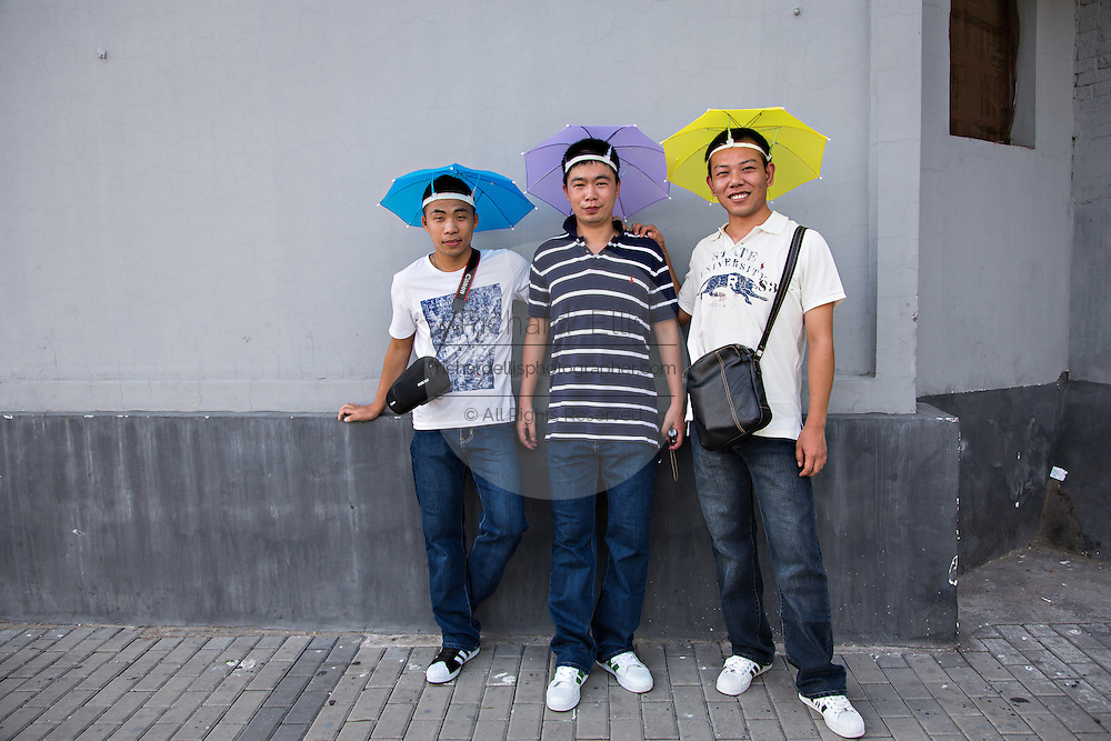 A group of Chinese tourists wearing umbrella hats in Beijing, China