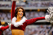 A Dallas Cowboys cheerleader performs during a timeout in a Christmas outfit at Cowboys Stadium in Arlington, Texas, on December 23, 2012.  (Stan Olszewski/The Dallas Morning News)
