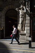 A businessman walks past an Atlantes figure by the sculptor H.A. Pegram 1896 at the entrance of Drapers Hall livery company in Throgmorton Street, on 17th Juy 2017, in the City of London, England. The Drapers' Company is a Livery Company in the City of London whose roots go back to the 13th century, when as its name indicates, it was involved in the drapery trade. While it is no longer involved in the trade, the Company has evolved acquiring a new relevance. Its main role today is to be the trustee of the charitable trusts that have been left in its care over the centuries. The Company also manages a thriving hospitality business. The first Drapers' Hall was built in the 15th century in St Swithin's Lane.  It bought a Hall on the present site in Throgmorton Street in 1543 from King Henry VIII for £1,200 about £350,000 in today's money. The Hall that the Company purchased from King Henry VIII in 1543 had been the private residence of Thomas Cromwell, Earl of Essex until his execution in 1540, when it was confiscated by the Crown.