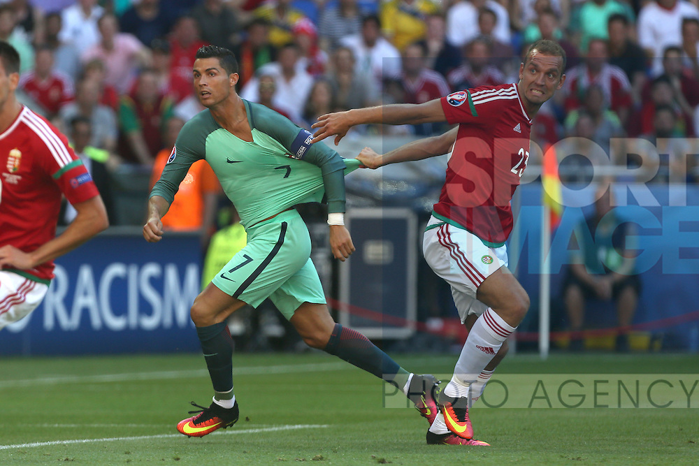 Roland Juhasz of Hungary tugs at the shirt of Cristiano Ronaldo of Portugal during the UEFA European Championship 2016 match at the Stade de Lyon, Lyon. Picture date June 22nd, 2016 Pic Phil Oldham/Sportimage