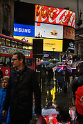 The brightly coloured advertising hoardings reflect off the wet pavement, on 4th November 2016, in Piccadilly Circus, London, England. The Circus is particularly known for its video display and LED signs which reflect off the pavement. As of 2016, the site has six illuminated advertising screens above three large retail units facing Piccadilly Circus on the north side. On special occasions the lights are switched off, such as the deaths of Winston Churchill in 1965 and Diana, Princess of Wales in 1997.