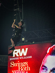 Image ©Licensed to i-Images Picture Agency. 29/06/2014. Manchester , UK . A spotlight operator climbs a rope ladder to his workstation , watched over by a giant Robbie Williams poster hanging over the stage , ahead of the start of the show . Robbie Williams Live Manchester. Robbie Williams performs at the Phones4U Arena in Manchester this evening (Sunday 29th June 2014) . Picture by i-Images