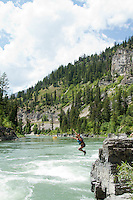 """Young woman jumping into the water near """"Lunch Counter Rapid"""" (class 3) on the Snake River near Jackson,  Wyoming."""