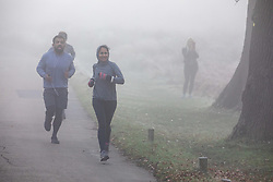 © Licensed to London News Pictures. 27/11/2020. London, UK. Runners enjoy an early morning jog through the fog in Richmond Park. Walkers, cyclists drivers and Black Friday shoppers were hit with dense fog and a heavy frost this morning as they did the daily commute through Richmond Park, South West London. Yesterday Health Secretary Matt Hancock set out his plans for the end of lockdown on the 2 of December and introduced a new Covid Tier 2 restriction system for London with shops, pubs and restaurants to open up again for the Christmas period. Photo credit: Alex Lentati/LNP