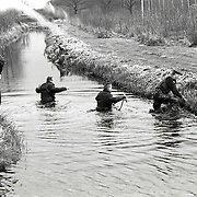 NLD/Ankeveen/19920323 - Arrestatieteam door het water en sloten voor zoekactie naar overvallers in de weilanden bij Ankeveen