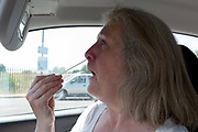 A middle-aged lady inserts a swab into her nose from the drivers seat of her car during a self-administered Coronavirus COVID-19 test in south London. There are four steps to the self-administered Covid-19 test inserting a swab into the nose and throat which the public works through in their car, windows up and all communications with army personnel via phone, in a south London leisure centre, on 2nd June 2020, in London, England. The kit provided consists of a booklet, plastic bag, swab, vial, bar codes and a sealable biohazard bag. The swab sample is taken from the back of the throat and nasal passage with the contents sealed and returned to soldiers through a narrow window. The whole process takes between 5-10mins with results available with 48hrs.