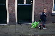 Een jongetje loopt met een koffertje achter zich aan door Utrecht...A boy is walking with a small suitcase in Utrecht.