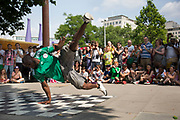 Break dance group One Motion Crew perform for money to a busy crowd of tourists on the Southbank, London, UK. This area has specific designated areas for performers to do their shows at specific times. The South Bank is a significant arts and entertainment district, and home to an endless list of activities for Londoners, visitors and tourists alike.