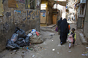 A woman walks past a pile of garbage at Shari Khayyamiya, a tentmakers street and market area in Cairo, Egypt.