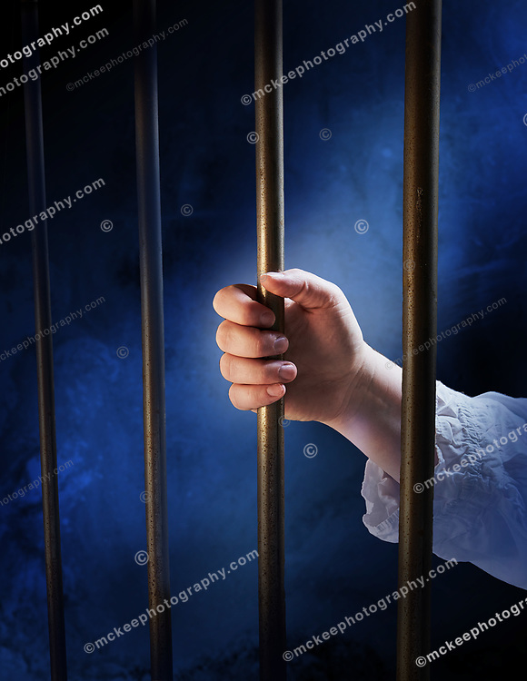A female hand loosely holding the bars of a prison cell, with moonlite background. Cold scene