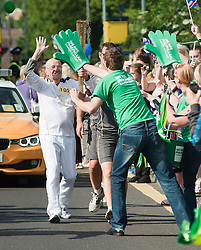 """The Olympic Torch relay reaches Sheffield on day 38 coverage from the Chapeltown - Ecclesfield - Parson Cross section of the Journey.<br /> Torch bearer number 105, 73 year old John Burkhill takes the flame on up towards Ecclesfield Schools main gate and gets a congratulatory """"hi Five"""" from a Macmillan Cancer Supporter."""