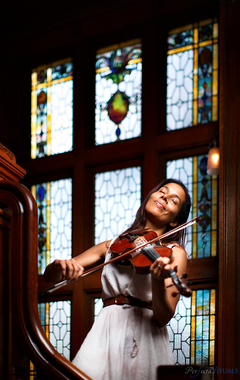 American musician Rhiannon Giddens plays her fiddle on the stairs of the Warfield House Bed & Breakfast in Elkins, West Virginia, Wednesday, August 5, 2015. Giddens was at a music workshop at  the Augusta Heritage Center of Davis & Elkins College in Elkins, West Virginia. Giddens was a founding member of the Grammy-winning band Carolina Chocolate Drops before embarking on a successful solo career.