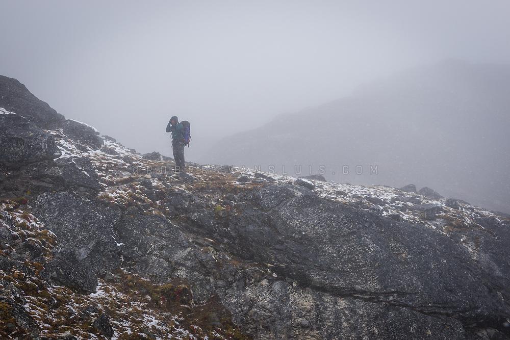 In the Nepal Himalaya, a hiker makes his way up to the Kongma La pass in snow. Photo © robertvansluis.com