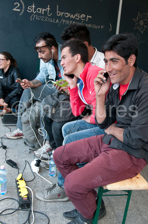 Hungary, Budapest, Keleti Station. Refugees  use free wifi provided by Greenpeace Hungary.