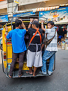 """03 APRIL 2015 - CHIANG MAI, CHIANG MAI, THAILAND: Men standing in the back of a """"songthaew"""" in the market in Chiang Mai, Thailand. A songthaew is pickup truck converted to use as a bus common in Thailand. Songthaew is a literal translation of """"two seats"""" because two bench seats are installed in the bed of the pickup.      PHOTO BY JACK KURTZ"""