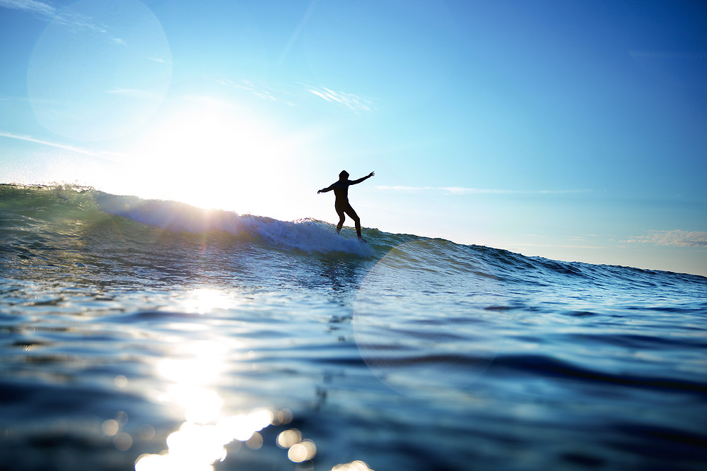 Silhouette of a surfer catching a wave with the sunlight shining behind him at St Ouen's  Bay, Jersey, CI