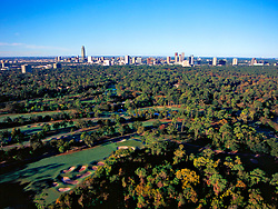 Aerial view of Houston's Galleria area skyline on the horizon with dense trees and a golf course in the foreground.
