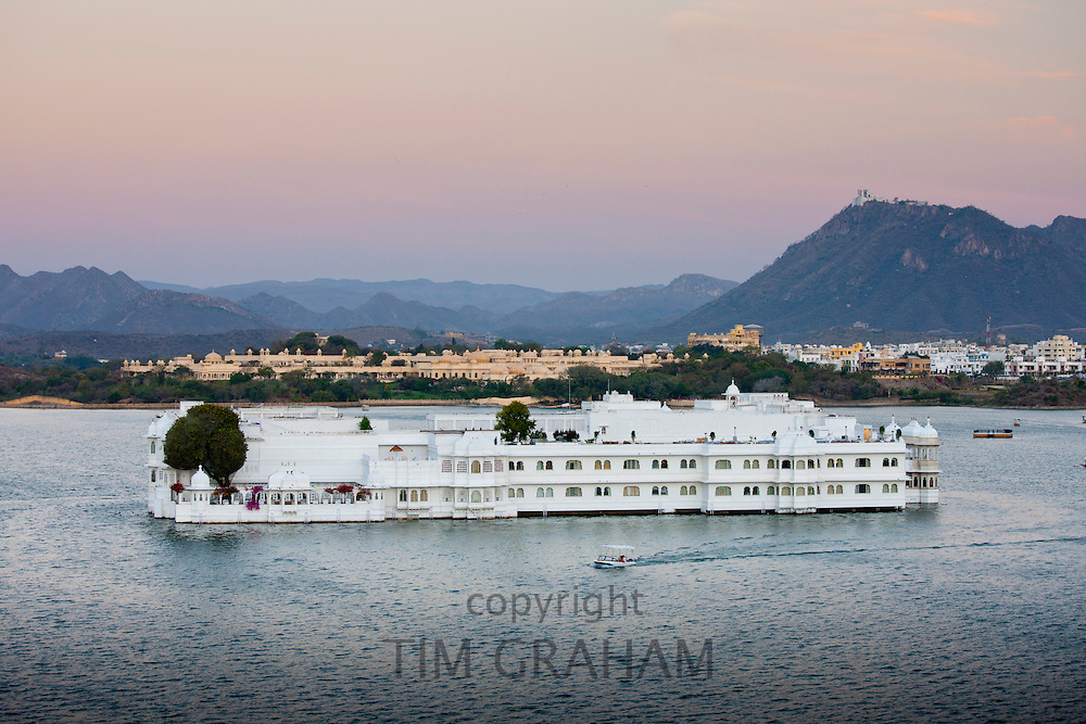 The Lake Palace Hotel, Jag Niwas, on island site on Lake Pichola in early morning with tourist boat leaving, Udaipur, Rajasthan, India