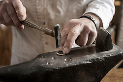 Mid section of craftsman shaping of copper ring at workshop, Bavaria, Germany