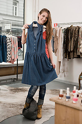 Young woman shopping in fashion store, smiling