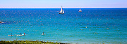 Sale boats and surfers in the Mediterranean sea Photographed in Herzliya beach, Israel