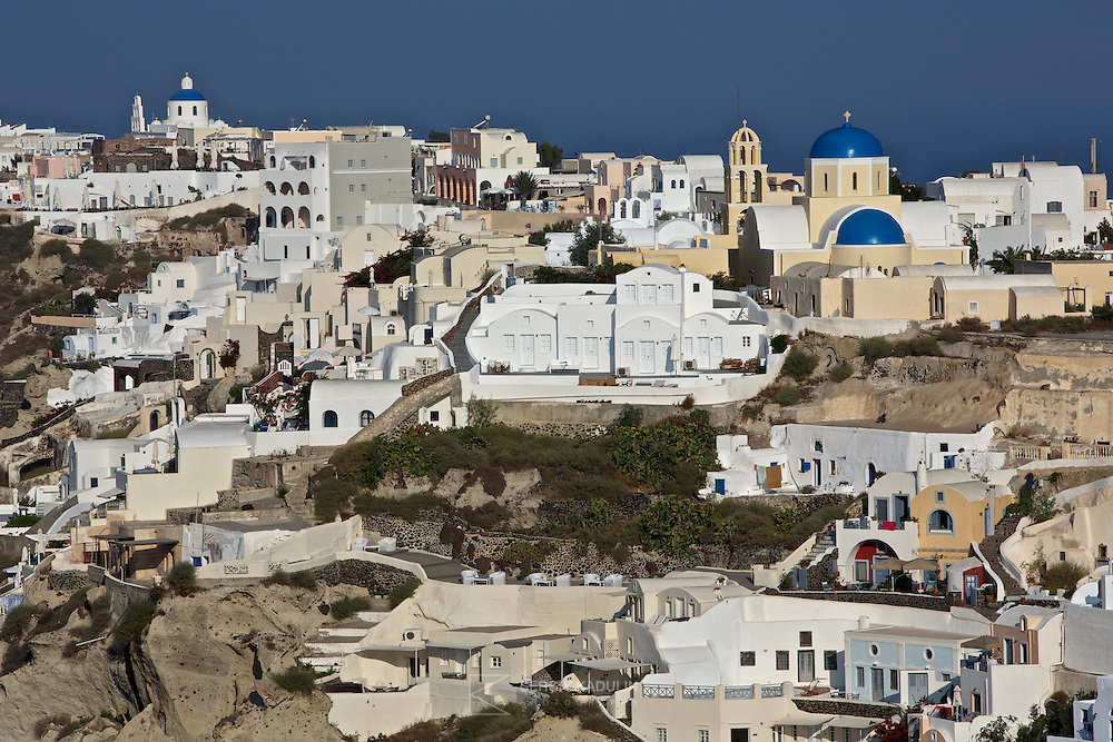 Residential area of Oia village on Santorini island, Greece. Morning sunlight cityscape view with white houses in the foreground and blue sea in the back.