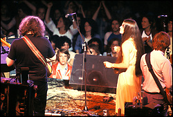 View of the Stage from behind. The Grateful Dead play the Providence Civic Center May 14, 1978. Back view of Jerry and Bobby. Side view of Donna. First several rows of fans clearly lit and thoughly enjoying the moment.