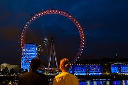 © Licensed to London News Pictures. 19/07/2012. London,UK.  London Eye Light Show.  Passers by stand before an illuminated London Eye.  EYE ON THE GAMES: Daley Thompson kicks off the world's first social media driven light show at the EDF Energy London Eye, powered by the UK's tweets on London 2012. The first EDF Energy of the Nation result reveals the nation is  62% positive about the Games with a week to go.    www.edfenergyofthenation.com  . Photo credit : Richard Isaac/LNP