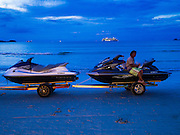 """26 DECEMBER 2014 - PATONG, PHUKET, THAILAND:  A beach worker rides on a trailer hauling """"Jet Ski"""" type water craft off the beach at Patong, on the island of Phuket in Thailand. Riding the water craft in the waters around the island is a popular past time for tourists.    PHOTO BY JACK KURTZ"""