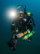 professional Scuba diver perform an underwater survey of the Mediterranean seabed. GoPro Action camera is attached to his wetsuit