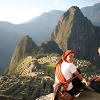 South America, Latin America, Peru, Machu Picchu. Two travellers overlooking the scenic citadel.