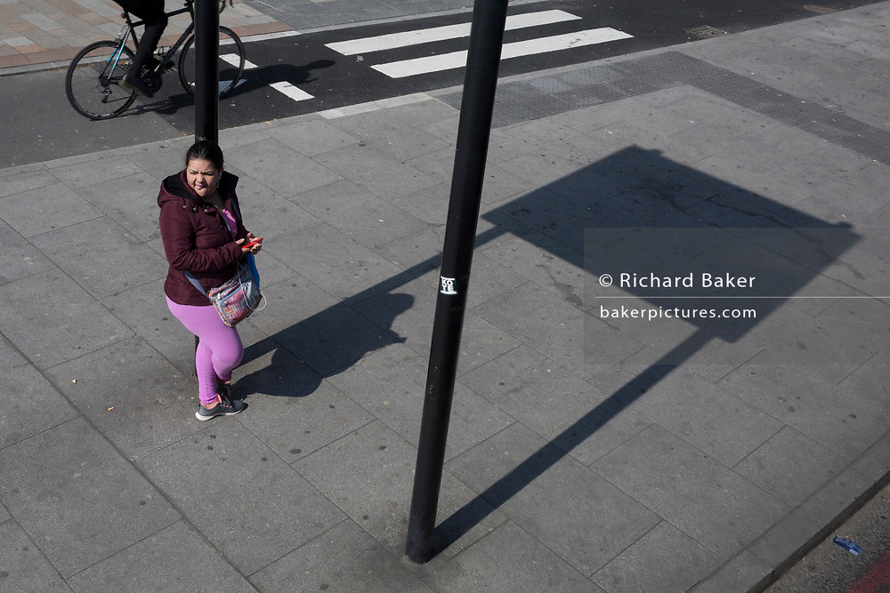 A woman waits for the next bus at Elephant & Castle, on 29th March 2019, in London, England.