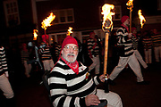 Lewes, Sussex. Bonfire Night November 5th 2013. Cliffe Bonfire Society members parade including John Russell in his wheelchair.