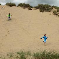 Europe, Ireland, Brittas Bay. Enjoying the steep dune of Brittas Bay.