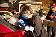 06 NOVEMBER 2020 - DES MOINES, IOWA: VIRGINIA BRYANT, a volunteer, puts cartons of frozen liquid eggs into a client's car during a drive through emergency food distribution at the Iowa State Fairgrounds Friday. A spokesperson for the Food Bank of Iowa said they had enough food for 1,500 families. Each family got frozen chicken legs, frozen liquid eggs, and fresh produce. There will be another emergency food distribution at the Fairgrounds on November 30. Food insecurity in the Des Moines area has skyrocketed since the start of the Coronavirus pandemic. Although unemployment rates in Iowa have fallen since a peak in June, many families that fell behind on rent are now facing eviction. The food bank spokesperson said use of the Food Bank's emergency pantries and distribution points is still increasing.    PHOTO BY JACK KURTZ