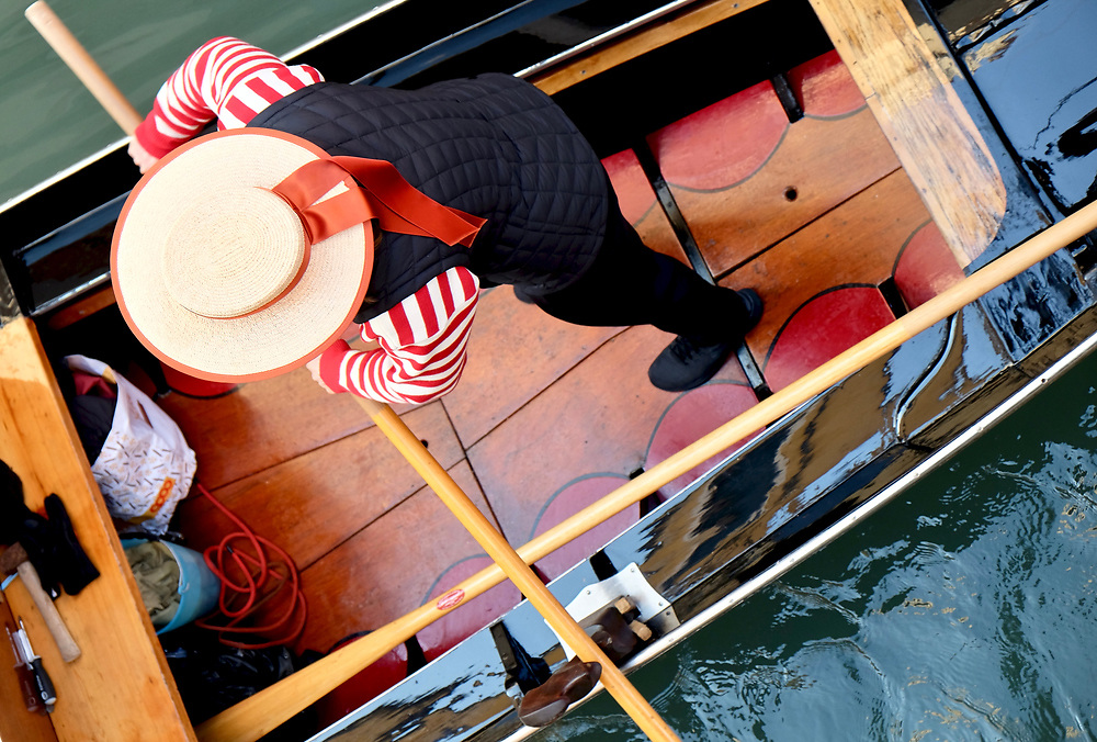 Gondola passing beneath a canal bridge in Venice.  This one piloted by one of a growing number of women joining the ranks of this traditionally male profession.