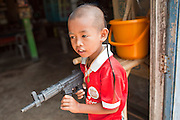 Apr. 3, 2010 - KHUN SAMUTCHINE, THAILAND: A boy plays with a toy gun in Khun Samutchine. Rising sea levels brought about by global climate change threaten the future of Khun Samutchine, a tiny fishing village about 90 minutes from Bangkok on the Gulf of Siam. The coastline advances inland here by about 20 metres (65 feet) per year causing families to move and threatening the viability of the village. The only structure in the village that hasn't moved, their Buddhist temple, is completely surrounded by water and more than 2 kilometers from the village. The temple and the village have asked the Thai government and several NGOs for help, but the only help so far is a narrow concrete causeway the government is building that will allow people to walk into the temple from a boat landing two miles away.  The walk to the village from a closer boat landing is shorter, but over an unimproved mud flat that is nearly impassible in the rainy season. PHOTO BY JACK KURTZ
