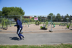 © Licensed to London News Pictures. 23/06/2020. London, UK. A man jogs past an outdoor gym in Chestnuts Park, north London, which has been closed and fenced since 23 March following the COVID-19 lockdown. Outdoor gym will re-open from 4 July as Prime Minister Boris Johnson outlines the plans to restore normal life after three months of coronavirus lockdown. Photo credit: Dinendra Haria/LNP