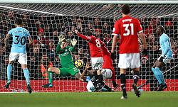 Manchester City goalkeeper Ederson saves a shot on goal by Manchester United's Juan Mata (centre)