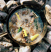 A meat and vegetable food dish is prepared over an open fire in Knoydart, in the highlands of Scotland, UK