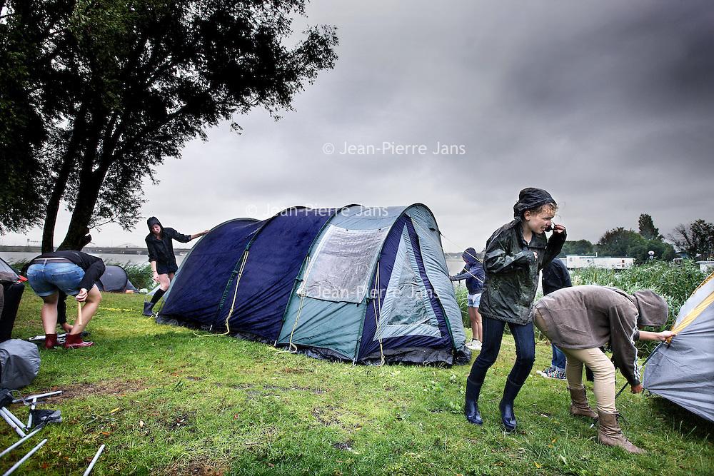 Nederland, Amsterdam , 14 juli 2011.. Buitenlandse vakantiegangers proberen in de storm en regen hun tent op te zetten op Camping Zeeburg..Foreign tourists trying to set up their tent at Camping Zeeburg in storm and rain.