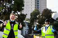 Victorian Trades Hall Council Secretary, Luke Hilakari (left) and owner of Macca Halal Foods, Abukar Hersi (right) pose for the camera as they finish unloading a truck full of donated halal meat for the Alfred Street residents who are still the subject of a hard lockdown during COVID-19 on 10 July, 2020 in Melbourne, Australia. Former Federal Labor Leader Bill Shorten, along with close allies at Trades Hall help deliver Halal meat, supplied by Macca Halal Foods to the locked down housing commission towers following a coronavirus outbreak detected inside the complex. Mr Shorten was able to use his high profile to ensure food was not turned away by police so that it would reach the residents inside. (Photo be Dave Hewison/ Speed Media)