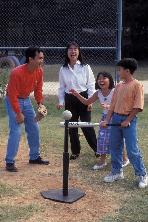 Vietnamese Family having fun playing T-Ball with kids.<br /> ©Bob Daemmrich/